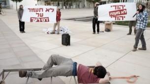 نشطاء من اليمين الاسرائيلي خلال مظاهرة دعم للمعتقلين المشتبه بهم في الهجوم على عائلة دوابشة من دوما يمثلون التعذيب المزعزم الذي يتلقاه المعتقلين. تل ابيب 23 ديسمبر، 2015  (Tomer Neuberg/Flash90)