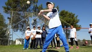 """طفل يستعد لصرب الطابة ضمن برنامج """"بيسبول للجميع""""، برنامج تعايش إسرائيلي. (Courtesy Association of Baseball in Israel)"""