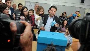 ايمن عودة، رئيس القائمة المشتركة يدلي بصوته برفقة ثلاثة اطفاله في الناصرة، 17 مارس 2015 (Basal Awidat/Flash90)