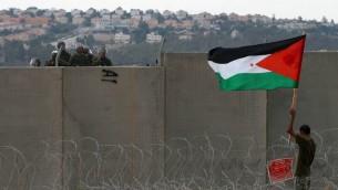 متظاهر فلسطيني يحمل علم بينما يقف بالقرب من الجدار الأمني خلال مظاهرة في بلعين، سبتمبر 2011 (Issam Rimawi/Flash90)