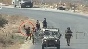 صورة مأخوذة من مشاهد تم إلتقاطها في الضفة الغربية في 5 سبتمبر، 2015، والتي تظهر جنديا إسرائيليا يقوم بإلقاء كاميرا تابعة لصحافيين من وكالة فرانس برس على الأرض. (لقطة شاشة: YouTube)