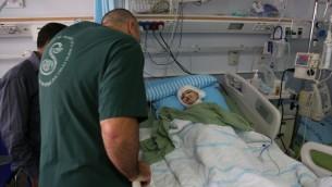 حسين دوابشة وطبيب بجانب سرير احمد دوابشة  في مركز شيبا الطبي في تال هشومير (Eric Cortellessa/Times of Israel)