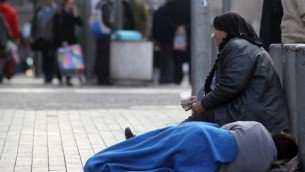 صورة توضيحية لسيدة فقيرة تقوم بالتسول في القدس. (Nati Shohat/Flash90)