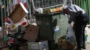 رجل مسن يبحث في حاويات القمامة بالقرب من سوق غذاء في مدينة بيتاح تيكفا في مركز اسرائيل، 24 يونيو 2015 (Nati Shohat/Flash90)