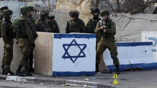 جنود اسرائيليون يحرسون في موقع وقوع محاولة هجوم طعن في مفترق بيت عينون بالقرب من الخليل، 12 يناير 2016 (AFP / HAZEM BADER)