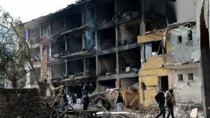 الشرطة التركية تتفحص الحطام الناتج عن تفجير سيارة مفخخة بجانب مركز للشرطة في دياربكر، 14 يناير 2016 (ILYAS AKENGIN / AFP)
