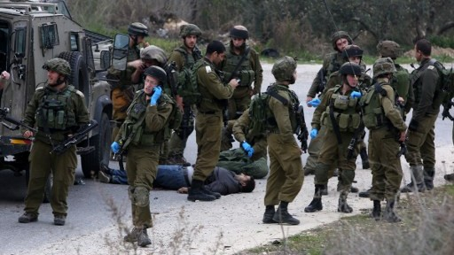 جنود اسرائيليون يحيطوت بجثمان معتدي فلسطيني قُتل بعد تنفيذه هجوم طعن بالقرب من نابلس في الضفة الغربية، 14 يناير 2016 (JAAFAR ASHTIYEH / AFP)
