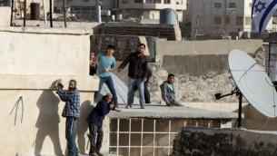 مستوطنون يهود يقفون على سطح مبنى بعد إقتحامهم لمنزلين وسط الخليل، 21 يناير، 2016. (AFP/Hazem Bader)