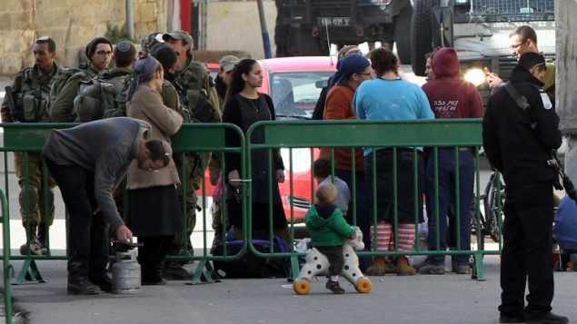 مستوطنون إسرائيليون يقومون بجمع أمتعتهم بينما تقوم قوات الأمن الإسرائيلية بعملية إخلاء من منزلين في قلب مدينة الخليل في الضفة الغربية، 22 يناير، 2016. (AFP/HAZEM BADER)