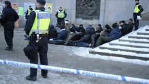 الشرطة السويدية تحيط بمجموعة معتقلين من النازيين الجدد الذين نظموا مسيرة غير معلن عنها في ستوكهولم في أعقاب مشاجرة في 23 يناير، 2016. (AFP/TT NEWS AGENCY/Jessica Gow)