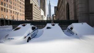 سيارات شرطة نيويورك مغطاة بالثلج بعد عاصفة تاريخية ضرب الساحل الشرقي للولايات المتحدة، 24 يناير 2016 (KENA BETANCUR / AFP)