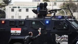 رجل مصري داعم للحكومة يقدم الازهار لقوات الشرطة الخاصة التي تحرس ميدان التحرير في القاهرة في يوم ذكرى الثورة، 25 يناير 2016 (MOHAMED EL-SHAHED / AFP)