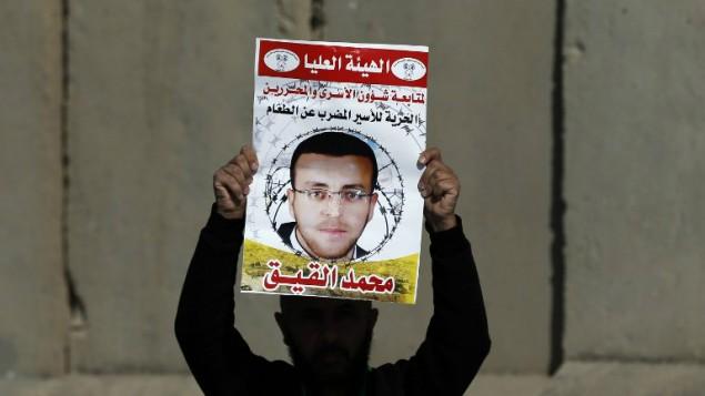 صورة تم إلتقاطها في 22 يناير، 2016، تظهر رجلا فلسطينيا يحمل لافتة تحمل صورة الصحافي الفلسطيني محمد القيق خلال تظاهرة بالقرب من رام الله للمطالبة بإطلاق سراحه من السجن الإسرائيلي. (Abbas Momani/AFP, File)