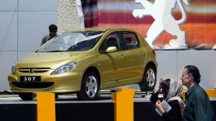 """(ارشيف) زوج إيراني ينظر الى سيارة بيجو 307 المصنعة في إيران على يد شركة """"ايران خودرو""""، في معرض السيارات السنوي في طهران، 22 يونيو 2004 (BEHROUZ MEHRI / AFP)"""