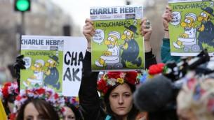 ناشطات 'فيمين' يرفعن عدد من صحيفة شارلي ايبدو خلال مسيرة الوحدة في باريس تكريما لضحايا الهجمات الارهابية التي اودت بحياة 17 شخصا في فرنسا، 11 يناير 2015 (AFP/LOIC VENANCE)