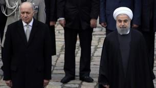 الرئيس الإيراني حسن روحاني يقف بجانب نظيره الفرنسي فرانسوا هولاند خال حفل تريحيبي في باريس، 28 يناير 2016 (LIONEL BONAVENTURE / AFP)
