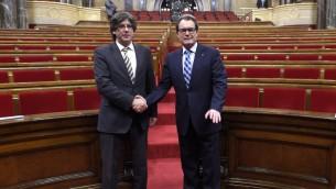 الرئيس المنتخب الجديد لاقليم كاتالونيا كارلس بوتشدمون (يسار) يصافح الرئيس الاقليمي المنتهية ولايته ارتور ماس في برلمان كاتالونيا في برشلونا، 1- يناير 2015 (CREDITLLUIS GENE / AFP)