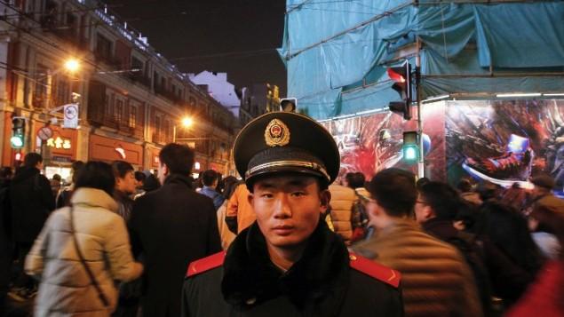 حارس امني يحرش الاحتفالات في شوارع شنغهاي، 31 ديسمبر 2015 (AFP Photo/STR)