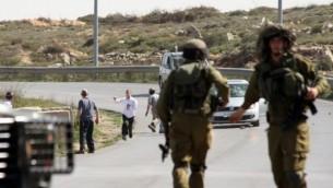 جنود إسرائيليون يقفون بالقرب من مستوطنين يقومون كما يبدو بمهاجمة سيارة مصور، بالقرب من مستوطنة بيت إيل بالضفة الغربية، 7 مارس، 2014. (AFP)