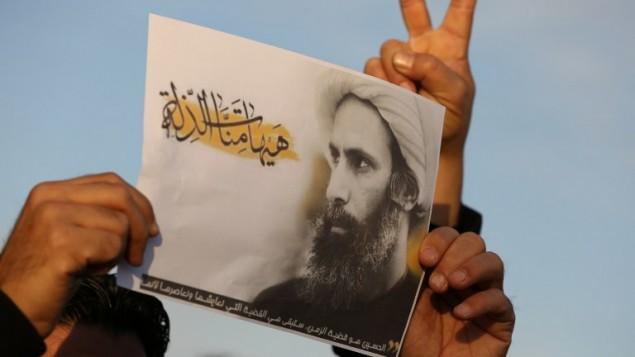 رجل عراقي  يحمل صورة رجل الدين الشيعي البارز نمر النمر خلال احتجاج على اعدامه من قبل السعودية، 3 يناير 2016 (AHMAD AL-RUBAYE / AFP)