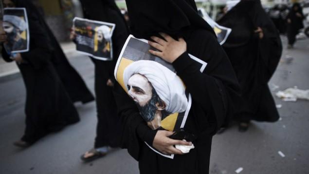 سيدة بحرينية تحمل صورة رجل الدين الشيعي البارز نمر النمر خلال احتجاج على اعدامه من قبل السعودية، 3 يناير 2016 (MOHAMMED AL-SHAIKH / AFP)