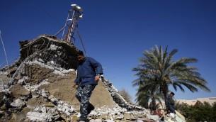 شرطي عراقي يتفحص حطام منسجد الفتح السني الذي تم تفجيره هلال الليل اثر التوترات الناتجة عن اعدام اليعودية لرجل دين شيعي، 4 يناير 2016 (HAIDAR HAMDANI / AFP)