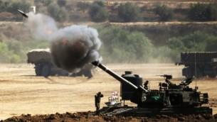 من الأرشيف: إطلاق قذيفة 155 مم من مدفعية إسرائيلية باتجاه أهداف من موقع بالقرب من الحدود مع قطاع غزة في 30 يوليو، 2014. (AFP/ JACK GUEZ)