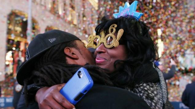 محتفلون يتعانقون بعد انتهاء العد التنازلي لبداية العام الجديد في ساحة تايمز سكوير في نيويورك، 1 يناير 2016 (AFP Photo/Kena Betancur)