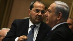 النائب العربي في الكنيست أحمد الطيبي (من اليسار) يتحدث مع رئيس الوزراء بينيامين نتنياهو خلال جلسة لجنة تحقيق برلمانية مخصصة للعنف المستشري في الوسط العربي، 13 فبراير، 2012. (Kobi Gideon/Flash90)