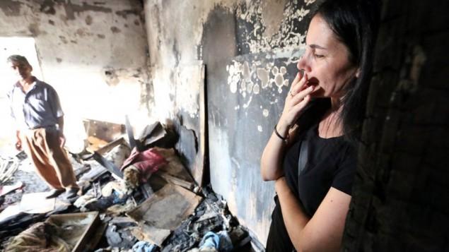 امرأة اسرائيليو تدخل منزل عائلة دوابشة في بلدة دوما في الضفة الغربية، 2 اغسطس 2015 (Yossi Zamir/Flash90)