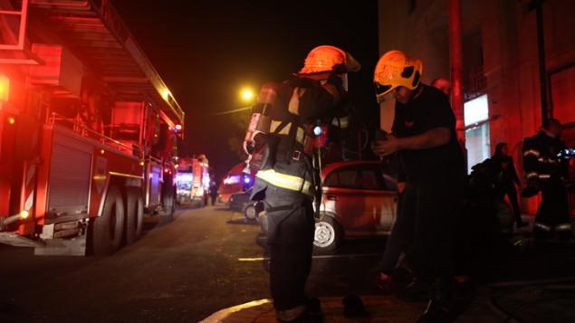 رجال الاطفاء يحاولون اخماد حريق في مبنى فيه مكاتب جمعية بتسيلم اليسارية، 10 يناير 2016 (Yonatan Sindel/Flash90)