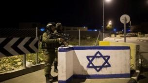 جنود إسرائيليون يقومون بالحراسة عند مفرق طرق في الضفة الغربية، 17 يناير، 2015. (Yonatan Sindel/Flash90)