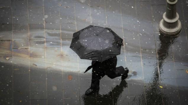 شخص يسير مع مظلة في وسط القدس مع بدء تساقط ثلوج خفيفة، 25 يناير، 2016. (Hadas Parush/Flash90)