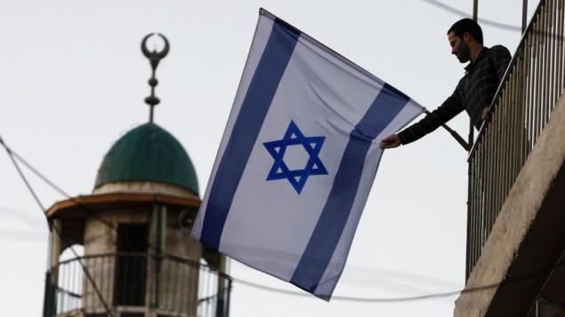 يهودي إسرائيلي يرفع العلم الإسرائيلي بالقرب من المدينة القديمة في القدس، التي شهدت تدفق سكان يهود على مناطق تسكنها أغلبية عربية. (Abir Sultan/Flash 90)
