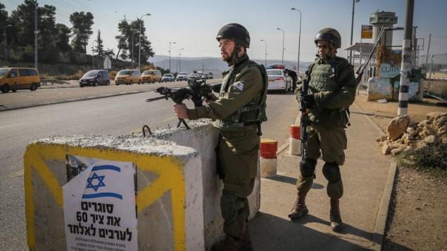 جنود إسرائيليون يقفون عند حاجز في مفرق غوش عتصيون، نقطة عبور رئيسية للضفة الغربية، 23 نوفمبر، 2015. (Gershon Elinson/FLASH90)
