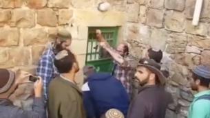 مستوطنون في الخليل يدخلون بالقوة إلى عدد من المباني بإدعاء أنه تم شراؤها بشكل سري في 21 يناير، 2016. (لقطة شاشة: YouTube)
