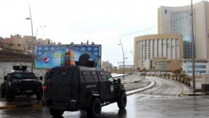 """قوات الأمن وخدمات الطوارئ الليبية تحيط فندق كورنثيا في طرابلس (من اليمين) في 27 يناير، 2015. الفندق تعرض لهجوم من قبل مقاتلي """"الدولة الإسلامية"""".  (AFP/Mahmud Turkia)"""