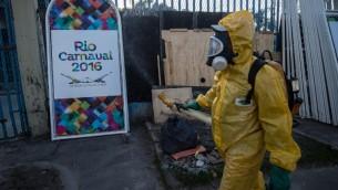 عامل في بلدية برازيلي يرش مواد مضادة للبعوض المسبب لفيروس الزيكا في ريو دي جنيرو، 26 يناير 2016 (CHRISTOPHE SIMON / AFP)
