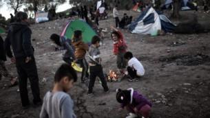 اطفال لاجئين ومهاجرين في حقل بالقرب من مخيم موريا في جزيرة ليزبوس اليونانية، 4 نوفمبر 2015 (ARIS MESSINIS / AFP)
