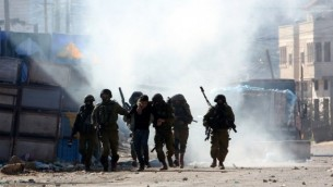 جنود إسرائيليون يعتقلون فلسطينيا خلال مواجهات في قباطيا، بالقرب من جنين في شمال الضفة الغربية، 4 فبراير، 2016. (Jaafar Ashtiyeh/AFP)