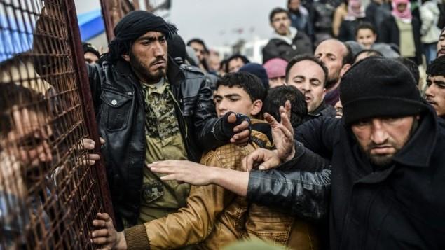 لاجئون فارون من مدينة حلب المحاصرة يتدافعون على الحدود السورية التركية اثناء انتظار الحصول على خيام، 6 فبراير 2016 (Bulent Kilic/AFP)