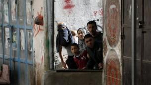 صورة توضيحية - فلسطينيون يشاهدون اشتباكات بين متظاهرين والجيش الإسرائيلي في مخيم الامعري بالقرب من رام الله في الضفة الغربية، 15 فبراير 2016 (ABBAS MOMANI / AFP)