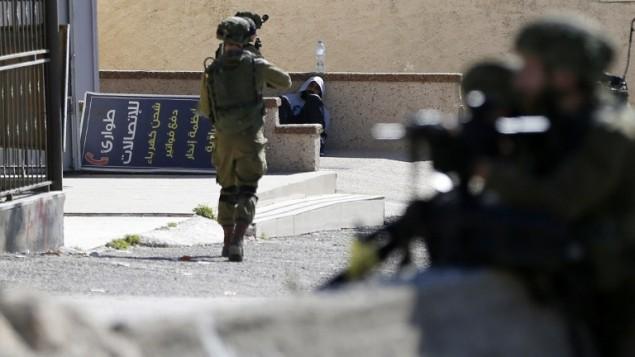 جندي اسرائيلي يوجه سلاحه نحو متظاهر فلسطيني قبل اعتقاله في مخيم الامعري بالقرب من رام الله في الضفة الغربية، 15 فبراير 2016 (ABBAS MOMANI / AFP)
