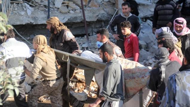 أشخاص يحملون نقالة وسط الحطام بعد تعرض مستشفى مدعوم من منظمة أطباء من دون حدود لغارات جوية يُشتبه بأنها روسية بالقرب من معرة النعمان، في محافظة إدلب الشمالية، 15 فبراير، 2016. (AFP / Omar haj kadour)