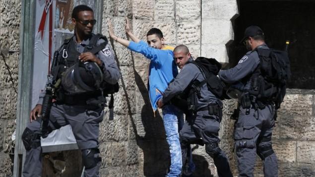 صورة توضيحية لعناصر شرطة يفتشون رجل فلسطيني في باب العامود في القدس، 17 فبراير 2016 (AFP / AHMAD GHARABLI)