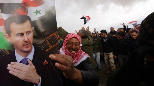 جنود متطوعون سوريون واقربائهم يرفعن الاعلام السورية وصور الرئيس بشار الاسد احتفالا بانتهاء تدريب عسكري اجراه الجيش السوري، 22 فبراير 2016 (AFP / LOUAI BESHARA)