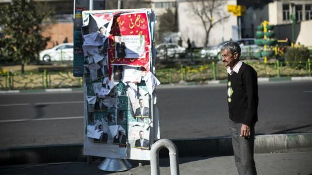 رجل إيراني يقف امام ملصقات مرشحين للانتخابات البرلمانية في طهران، 25 فبراير 2016 (Behrouz Mehri/AFP)