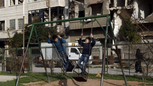 أطفال سوريون يلعبون على الأرجوحة في حديثة في بلدة الدوما التي يسيطر عليها المتمردون، على الأطراف الشرقية للعاصمة دمشق، 27 فبراير، 2016. (AFP / Sameer Al-Doumy)