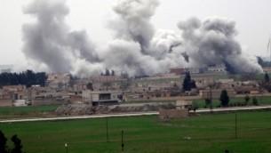 صورة مأخوذة في 27 فبراير، 2016 من بلدة اقجة قلعة في محافظة  أورفة التركية تظهر الدخان المتصاعد من حي في مدينة تل أبيض خلال إشتباكات بين تنظيم 'الدولة الإسلامية' ووحدات الحماية الشعبية. (AFP / STR)