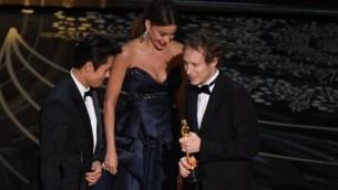 """الممثلة صوفيا فيرغارا والممثل بيونغ هو لي يقدمان جائزة أفضل فيلم أجنبي، """"سان أوف شول""""، امخرج الفيم لازلو نيميس (من اليمين) على منصة حفل توزيع  جوائز الأوسكار ال88 في مسرح دولبي، 28 فبراير، 2016، في هوليوود، كاليفورنيا. (AFP PHOTO / MARK RALSTON)"""